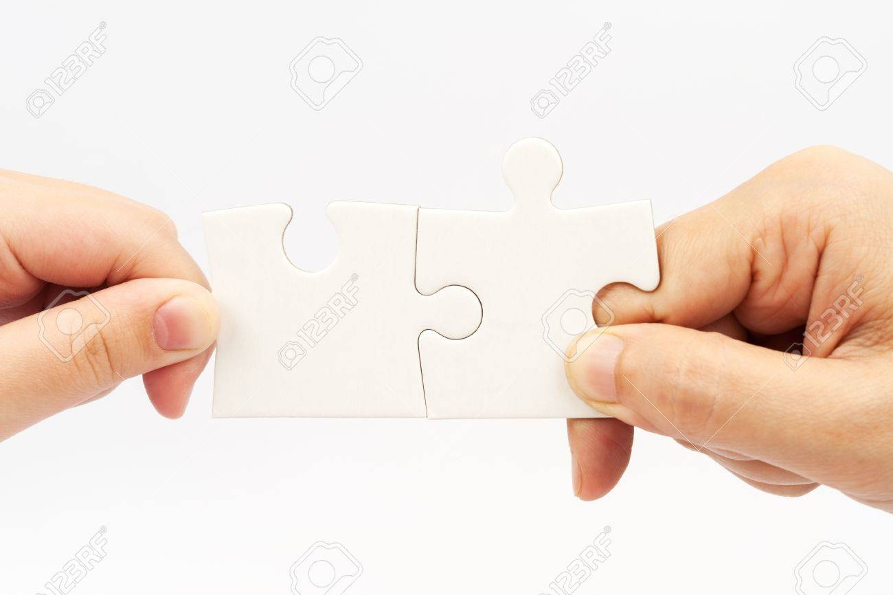 two hands holding puzzle pieces and connecting them stock photo