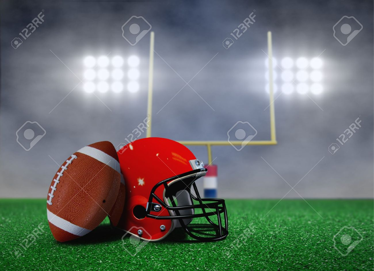American Football and Helmet on Field with Goal Post under Spotlights - 22731891