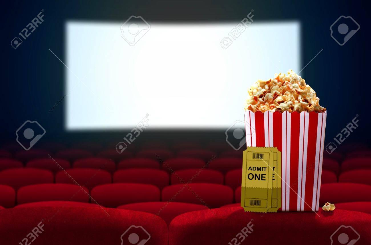 Cinema seat and pop corn facing empty movie screen - 57420003