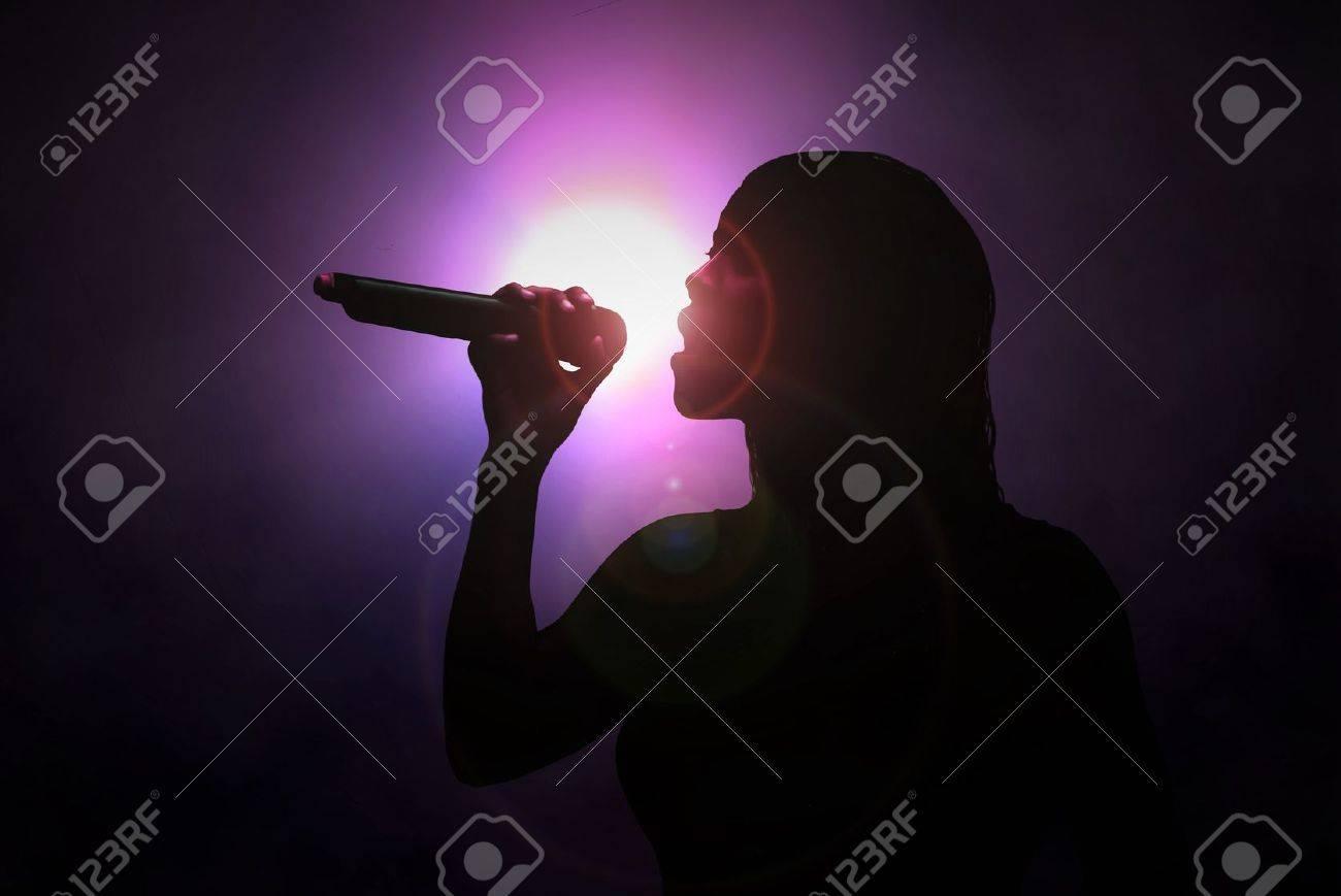 Women singing with microphone under spotlight - 57625007