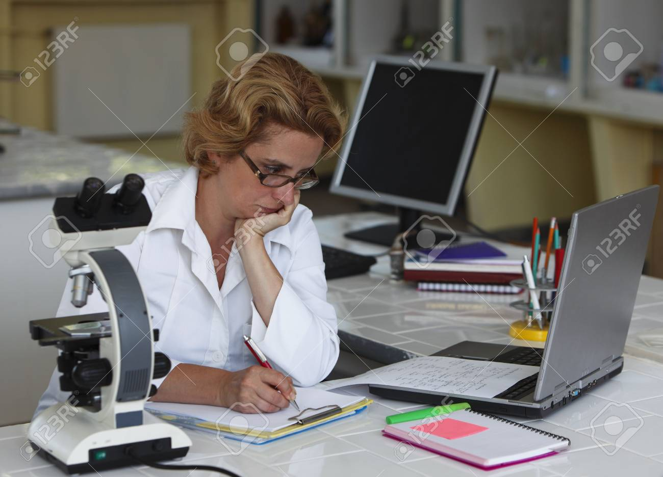 Female researcher taking notices at her workplace in a laboratory.All inscripstions are mine. Stock Photo - 5679845