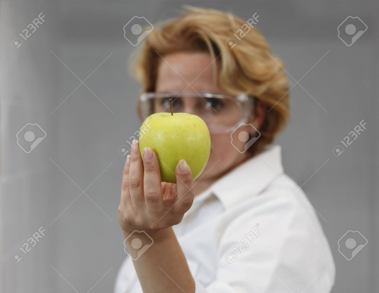 Image of a female researcher offering a tomato and an apple to suggest the idea that healthy eating is recommended also by scientists.Specific lighting for a classical research laboratory. Stock Photo - 6400711
