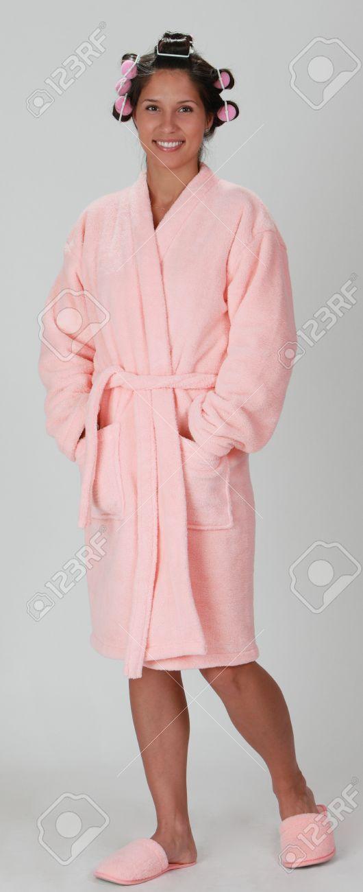 bae993147dc20a Junge Frau in einem rosa Plüsch Bademantel mit Lockenwickler stehend vor  einem grauen Hintergrund. Standard
