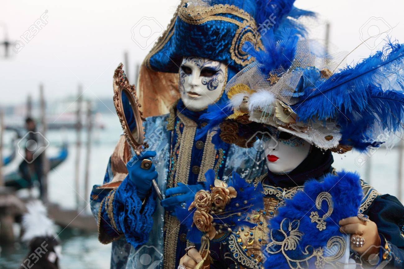 Venice,Italy,February 26th 2011:Two Venetian masks posing near the pagoda's port in San Marco Square in Venice during the carnival days.Selective focus on the first mask from left.The Carnival of Venice (