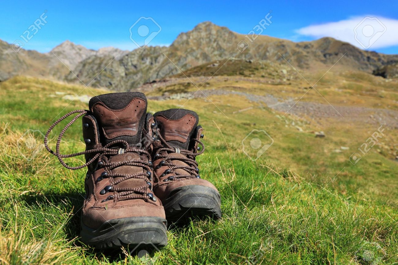 Image of a pair of hiking boots lying in the grass in front of a beautiful mountainous landscape in Pyrenees Mountains. Stock Photo - 10675373