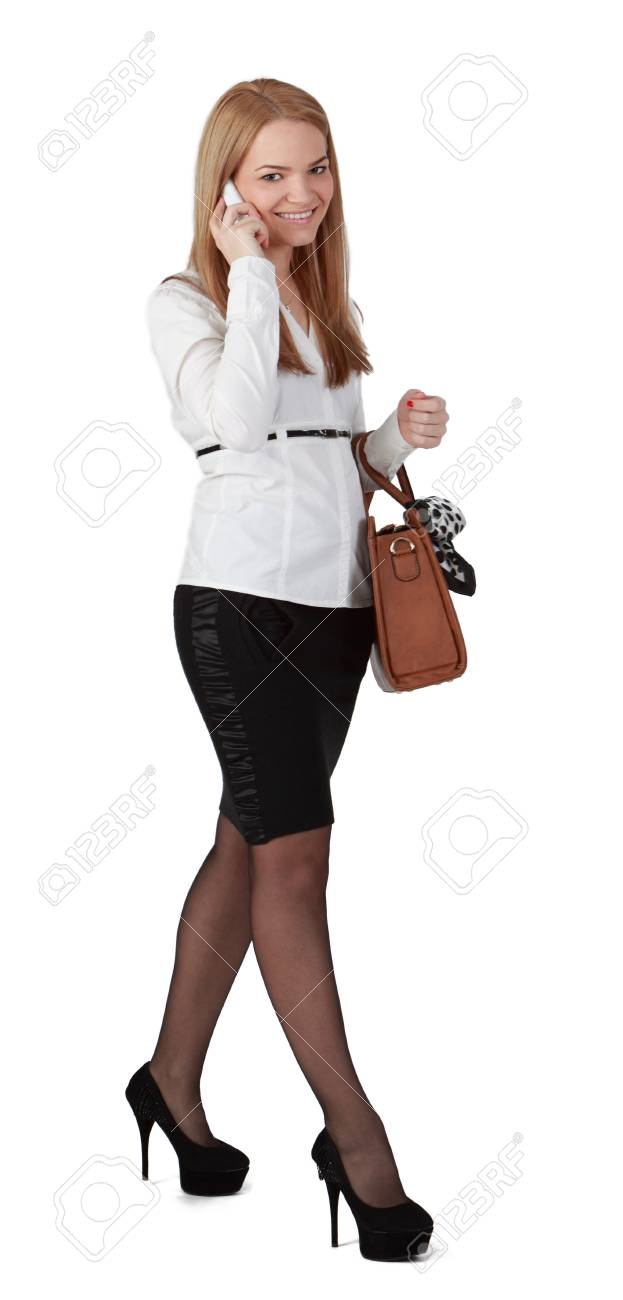 Young blonde woman using a mobile while walking against a white background. Stock Photo - 13026490