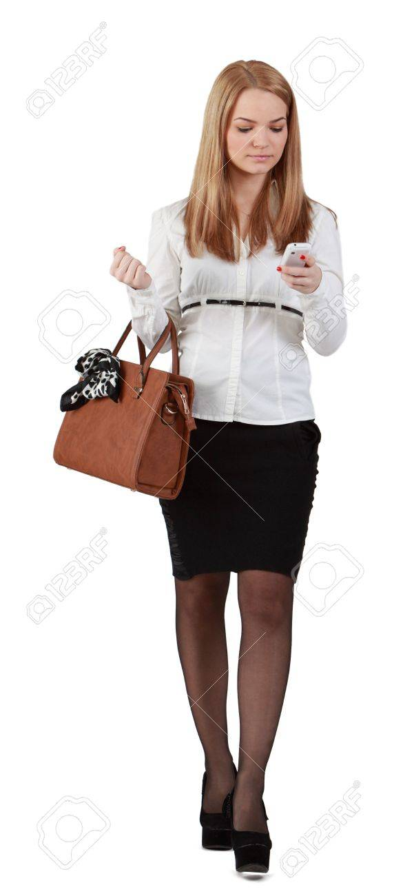 Young woman reading a phone message while walking against a white background. Stock Photo - 13026487