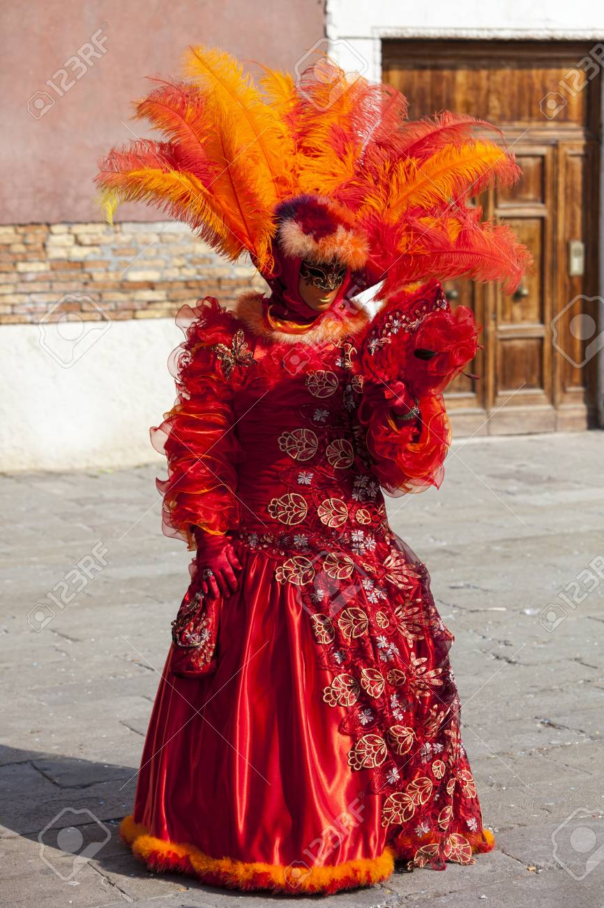 Venice, Italy- February 18th, 2012: Image of a person in a beautiful red Venetian costume posing with a mirror in Sestiere Castello during The Venice Carnival days. Stock Photo - 17914334