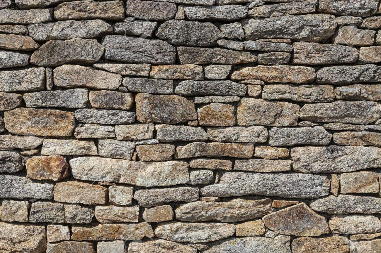 Muro Fatto In Pietra primo piano di un muro fatto di pietre di granito senza cemento,  caratteristica per le costruzioni nella bretagna nel nord-ovest della  francia.