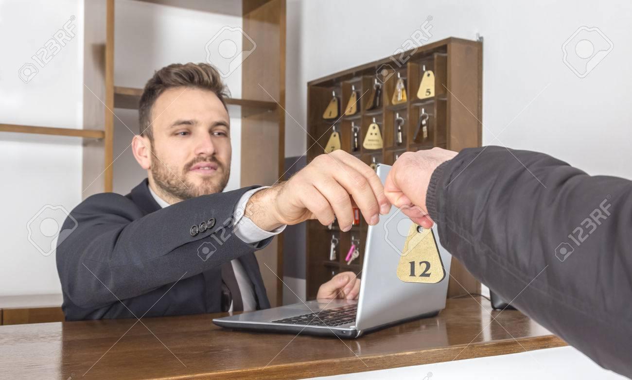 Image d une réceptionniste à son bureau donnant la clé d un client