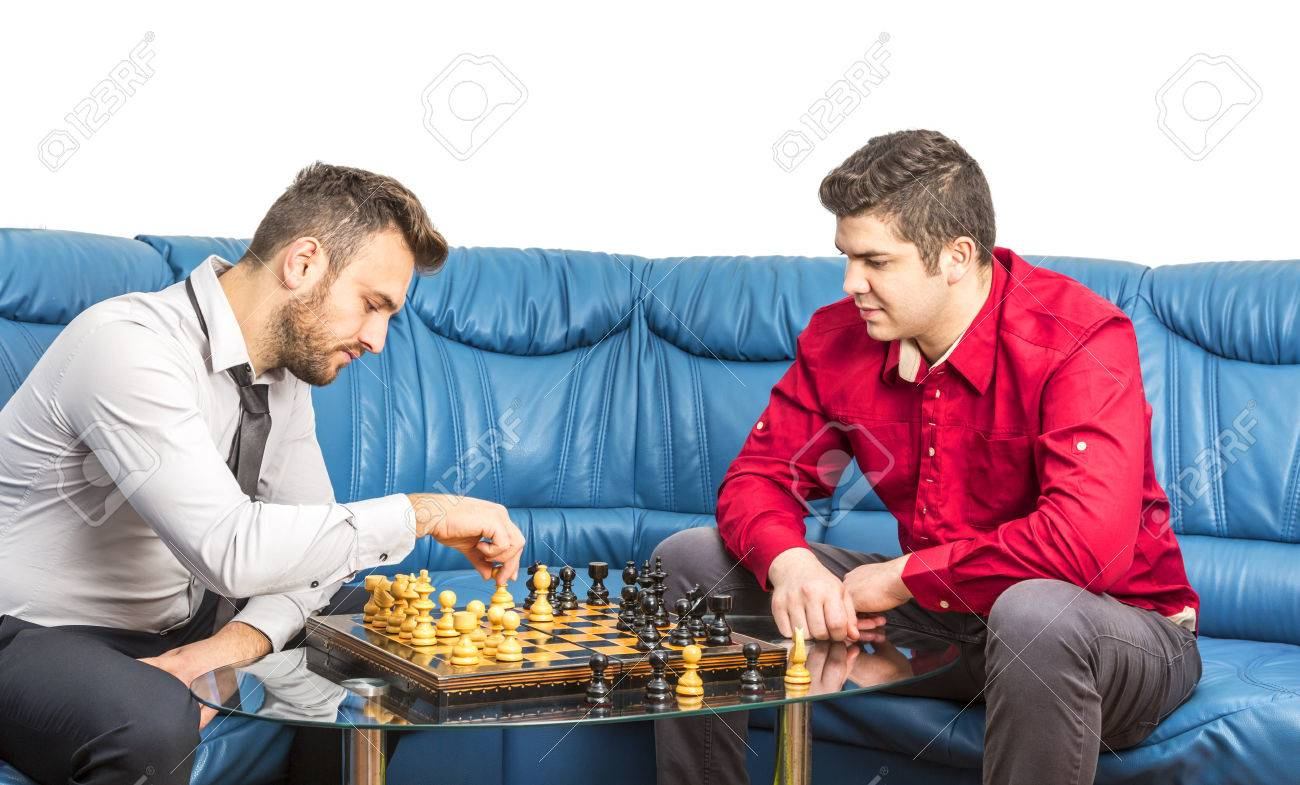 Two friends playing chess on a blue couch