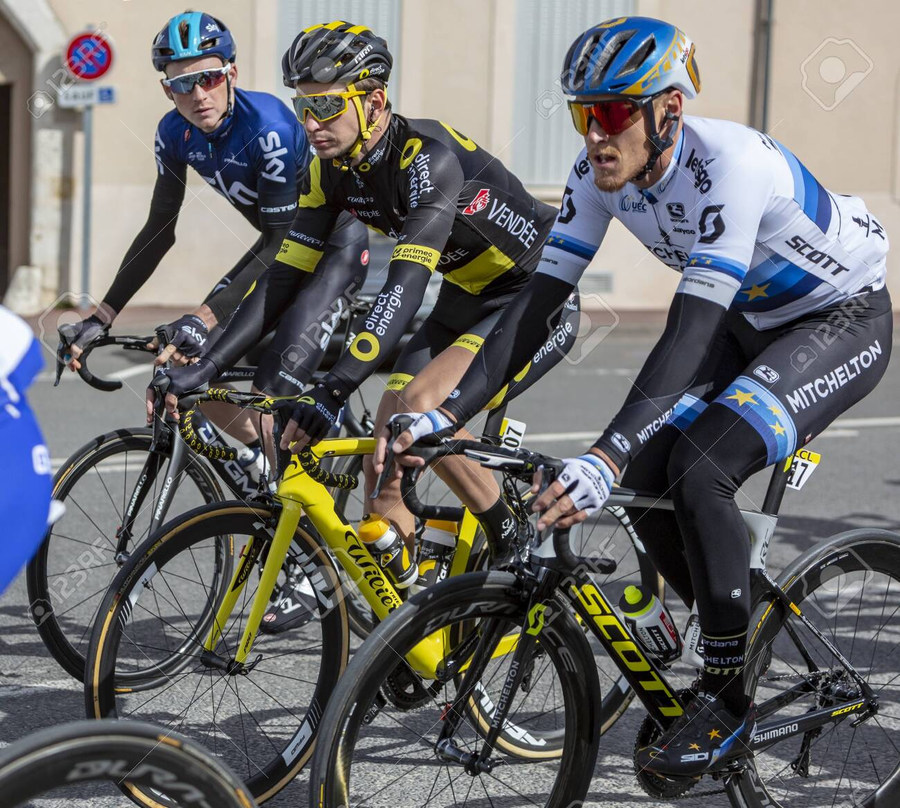 Chatillon-Coligny, France - March 10, 2019: Three cyclists (Matteo Trent of Mitchelton-Scott Team, Anthony Turgis of Direct Energy Team, Tao Geoghegan Hart of Sky Team) riding in the peloton, in Chatillon-Coligny during the stage 3 of Paris-Nice 2019. - 126924395
