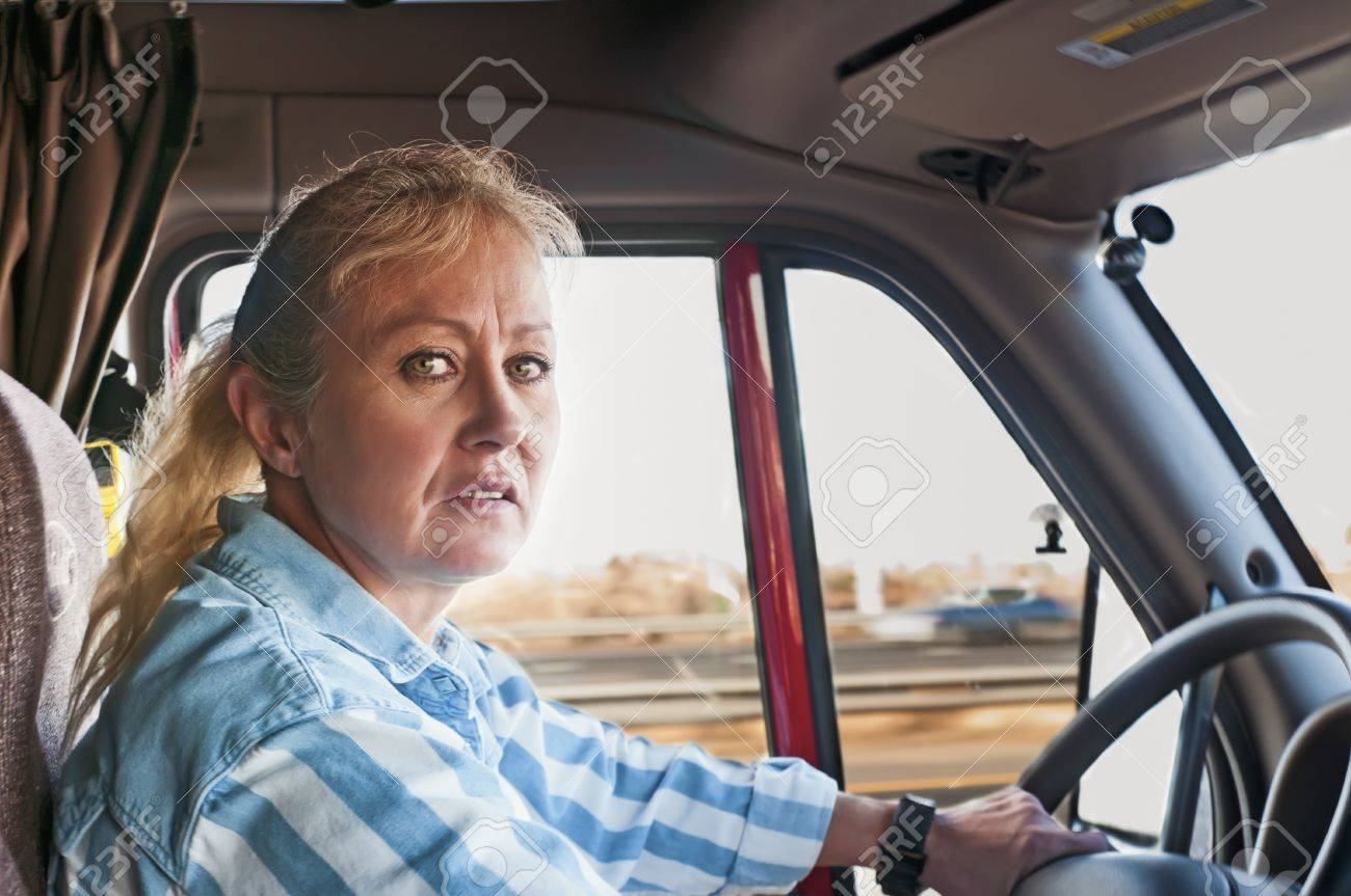 Female truck driver pretty adult woman driving a big truck down the highway stock