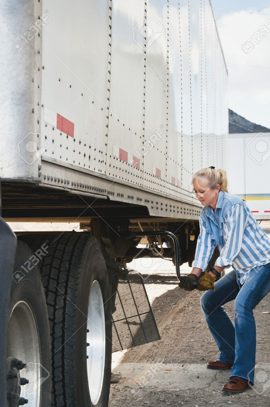 Pretty blonde woman truck driver cranking the dolly handle to raise the legs of a traier after backing her tractor under it. Stock Photo - 11291822