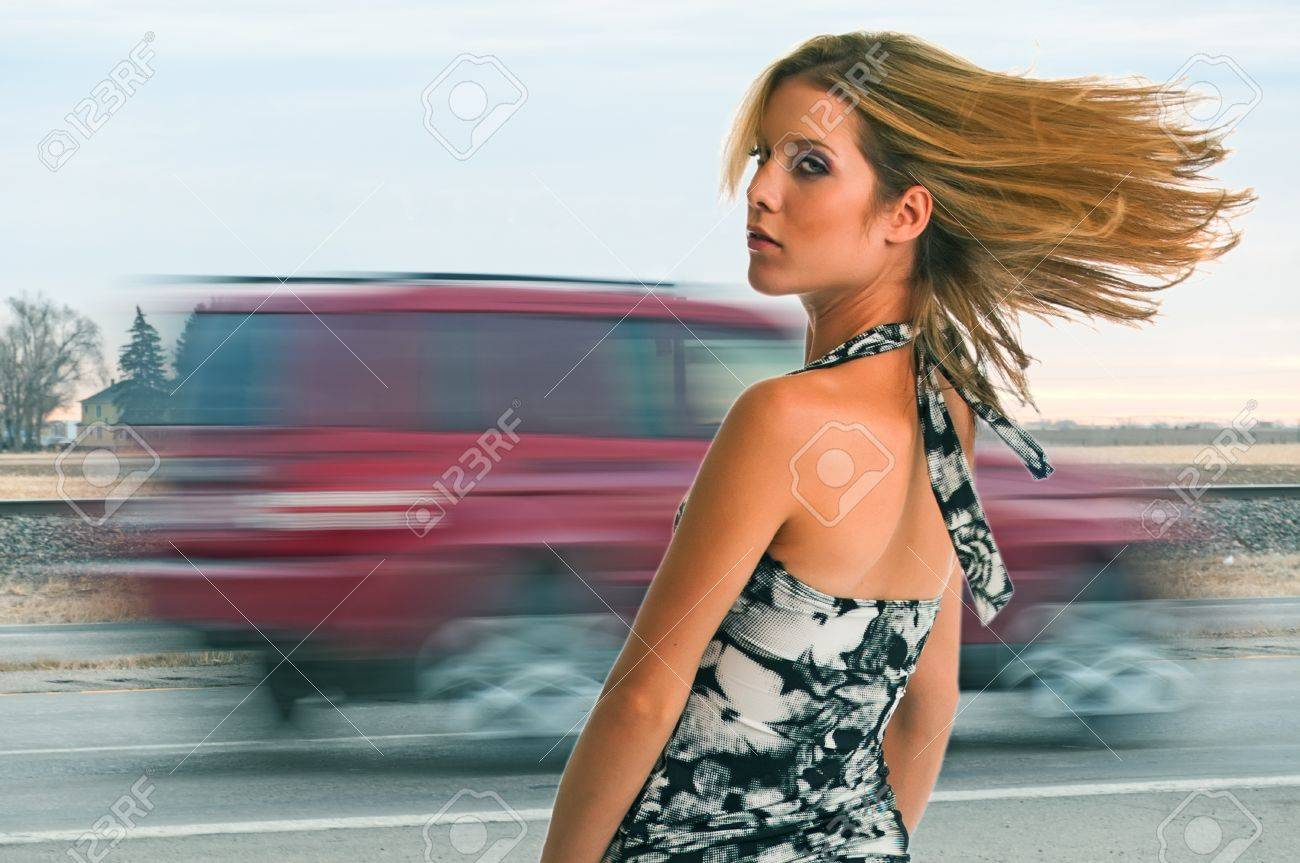 4a7f8308756 스톡 콘텐츠 - 예쁜 금발의 소녀 서 근처 빠른 그녀의 머리 트래픽이 흐르는 움직이는 자동차. 빠르게 움직이는 세계에서 확고한 발판.  소녀는 접지 튼튼합니다.