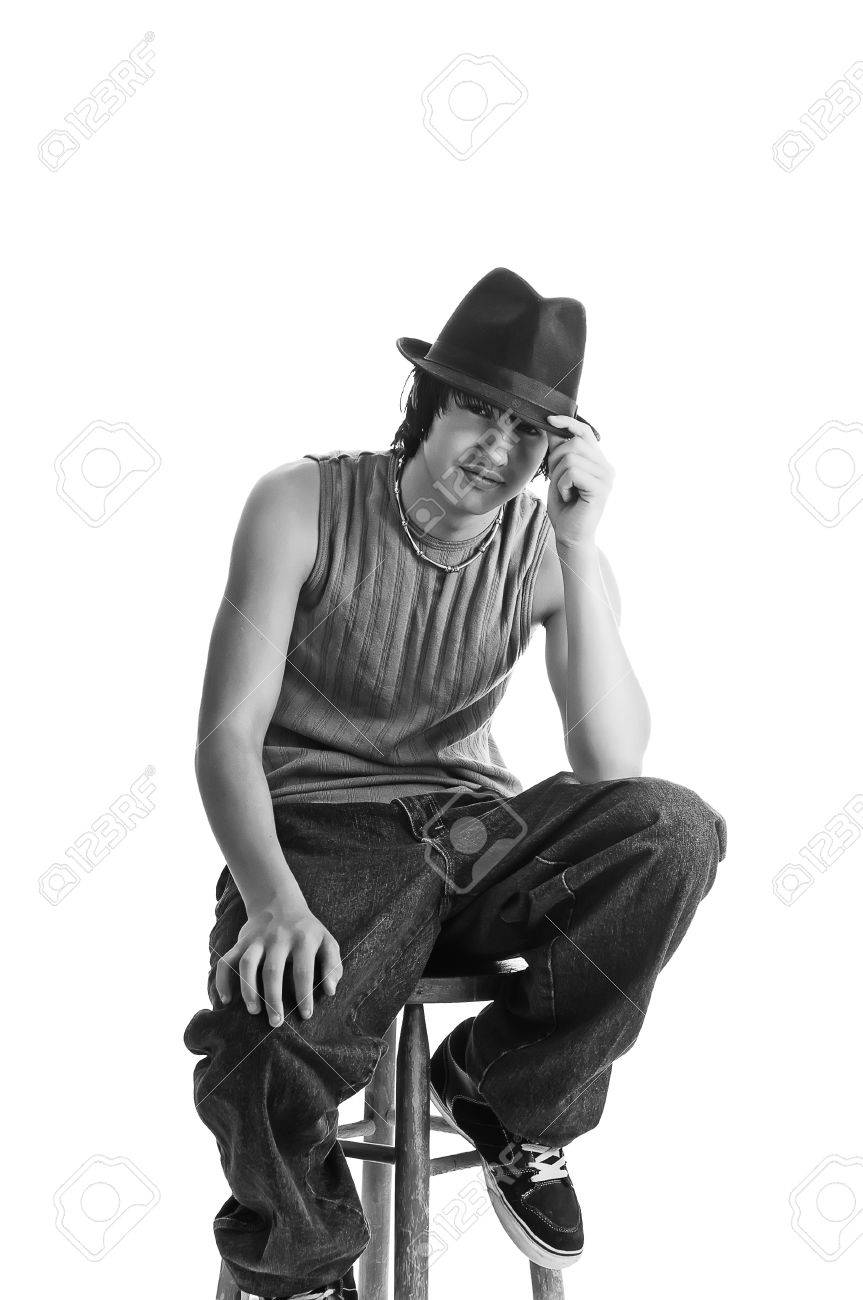 Handsome young man sitting cool in a fedora on a stool. Isolated on a white background. Black and White. Stock Photo - 11960353