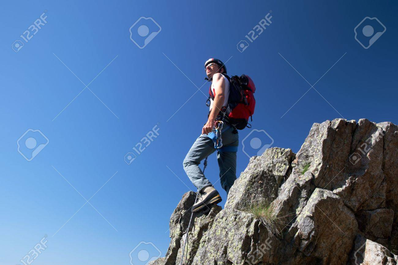 Climber standing on a stone at the top of his route, over a deep blue sky. Stock Photo - 3412416