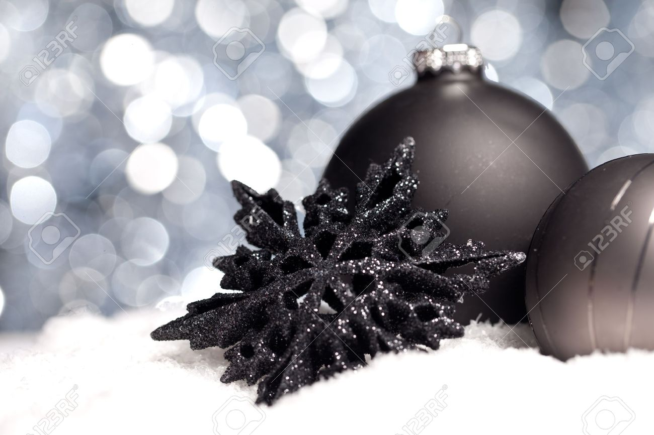 Black Christmas Balls.Two Black Christmas Balls With Christmas Star On Snow With Bokeh