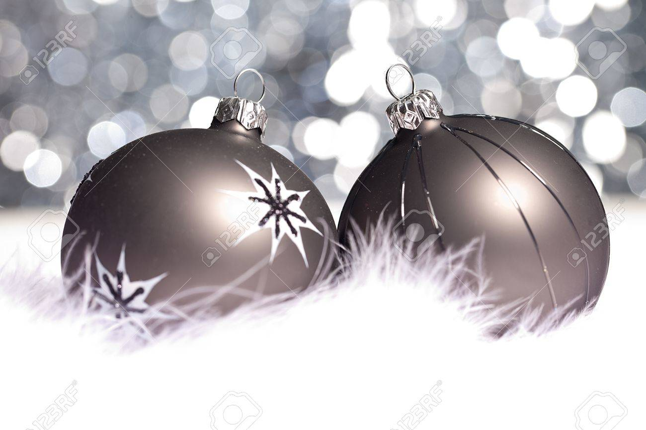 Black Christmas Balls.Two Black Christmas Balls On Snow Background With Bokeh
