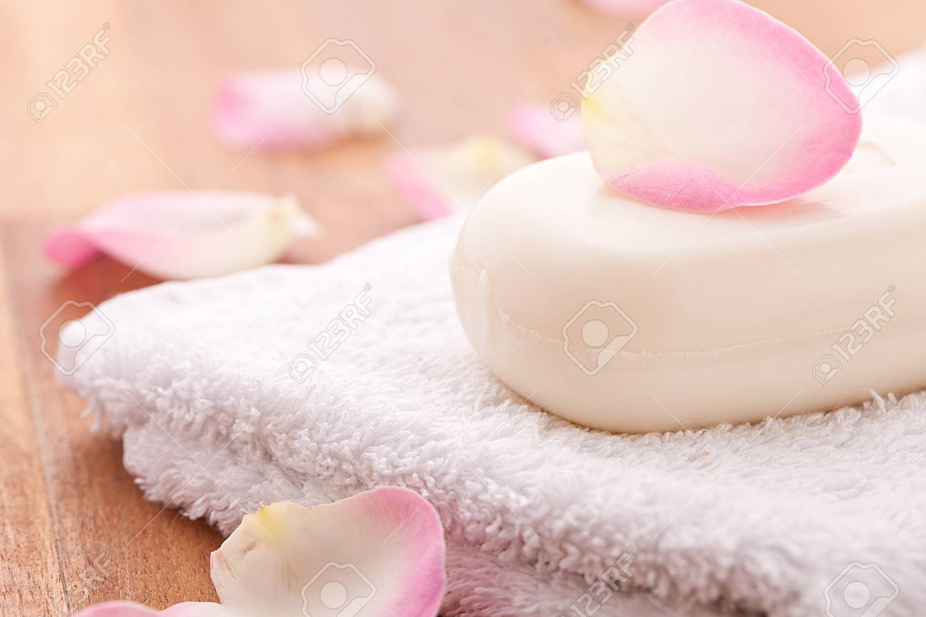 soap with rose leafs on towel and wooden background Stock Photo - 12508223