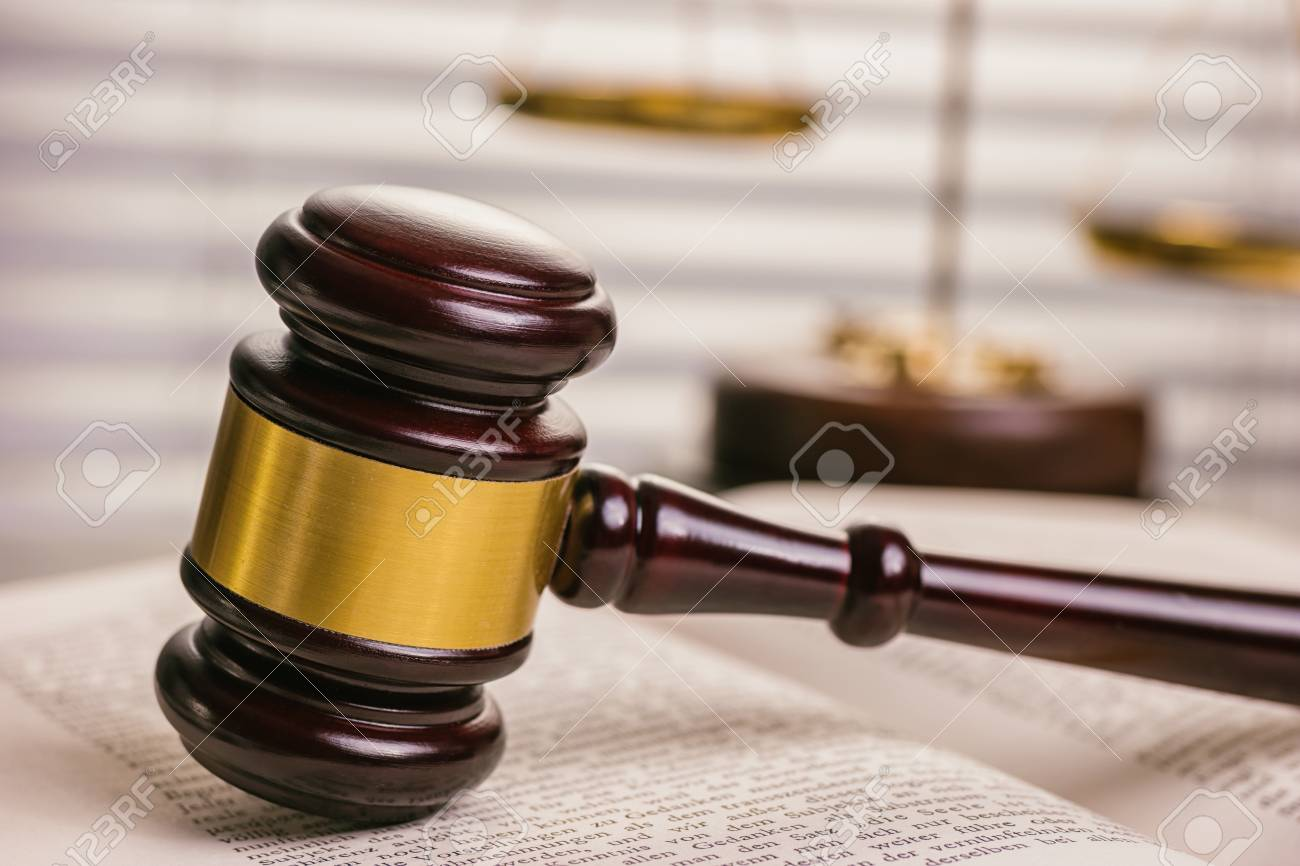 Closeup Of A Open Law Book With Judges Gavel Scale Stock Photo