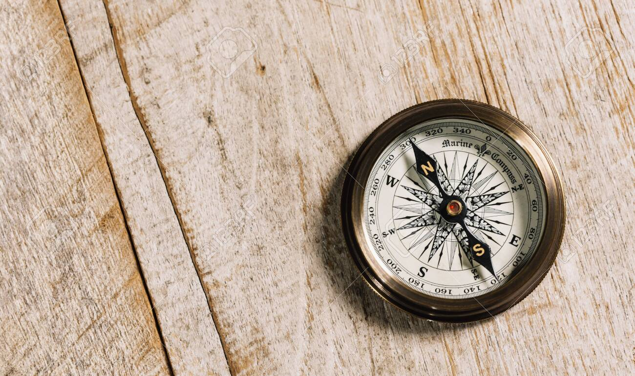 Old compass on wood background concept for direction, travel, guidance or assistance - 136736605