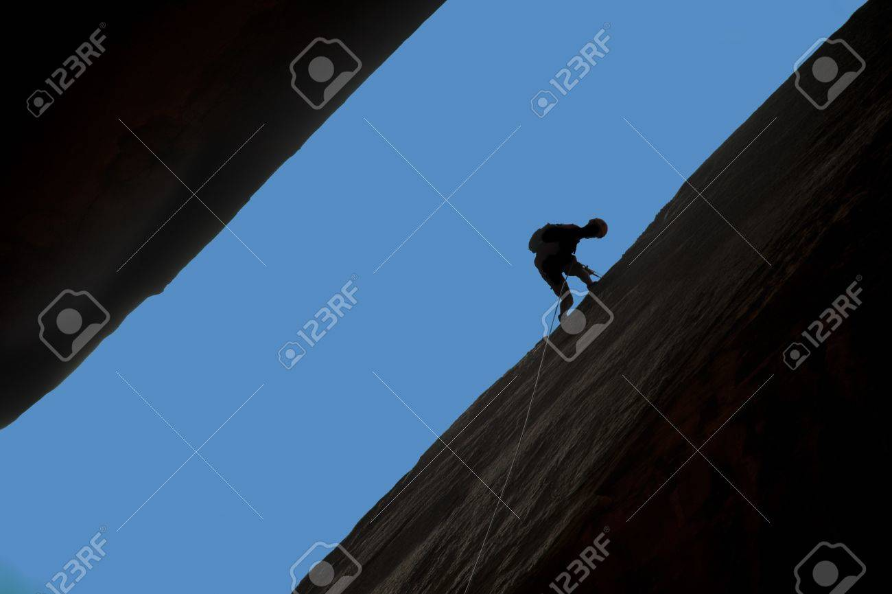Silhouette of rock climber rappelling a crack with blue sky behind