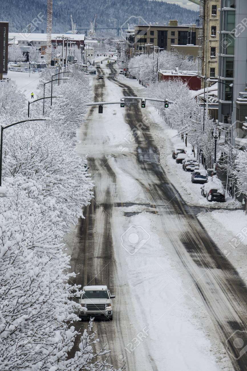 Car Traffic On Snowy Winter Street In Portland Oregon Stock Photo