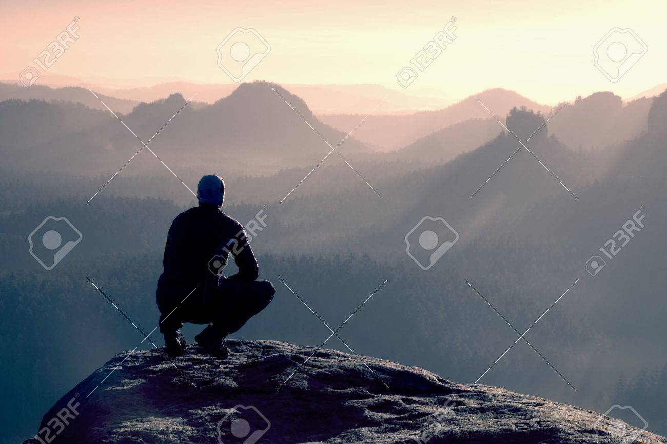 Young man in black sportswear is sitting on cliff's edge and looking to misty valley bellow - 47642819