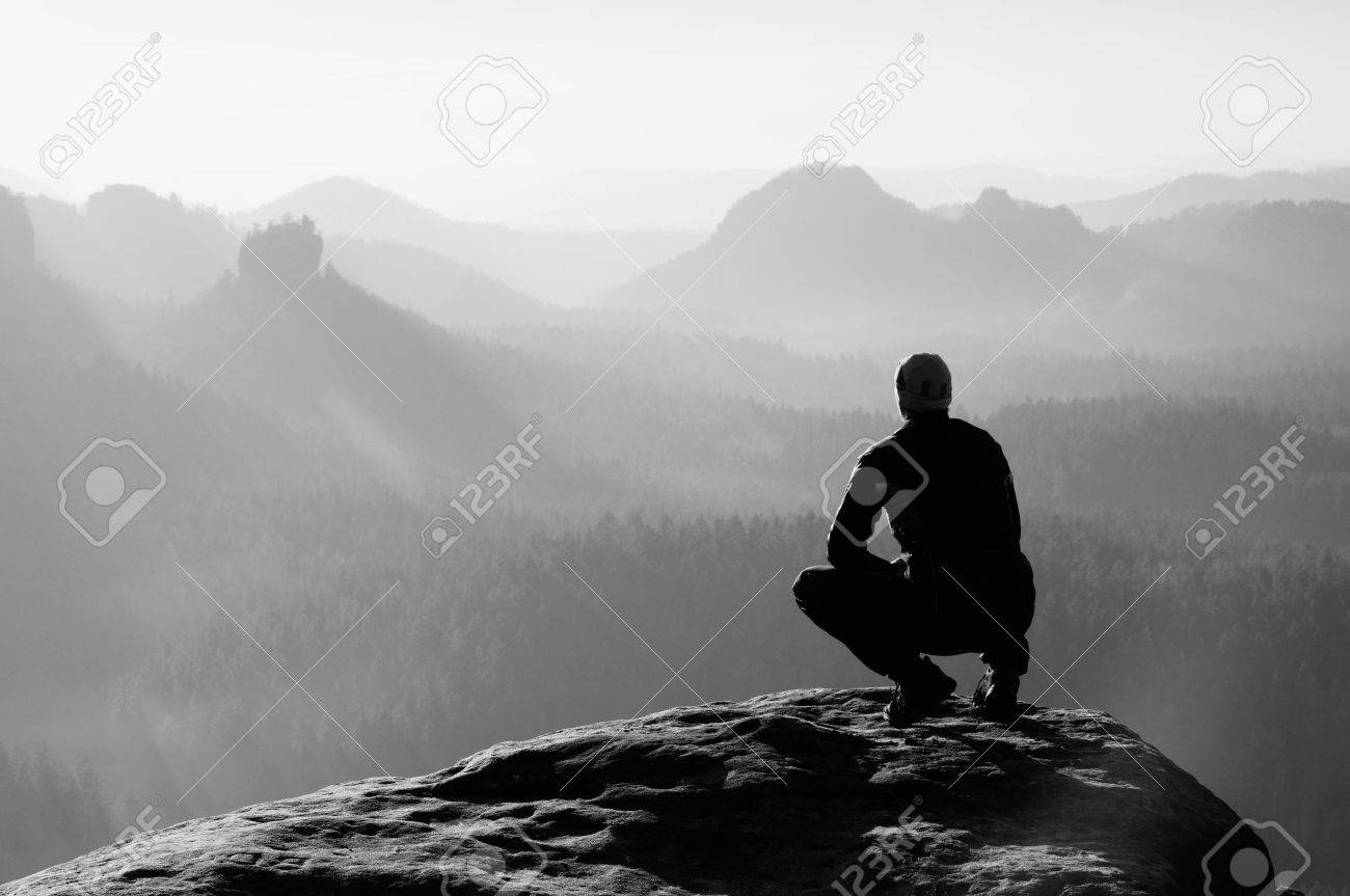 Young man in black sportswear is sitting on cliff's edge and looking to misty valley bellow - 47642821