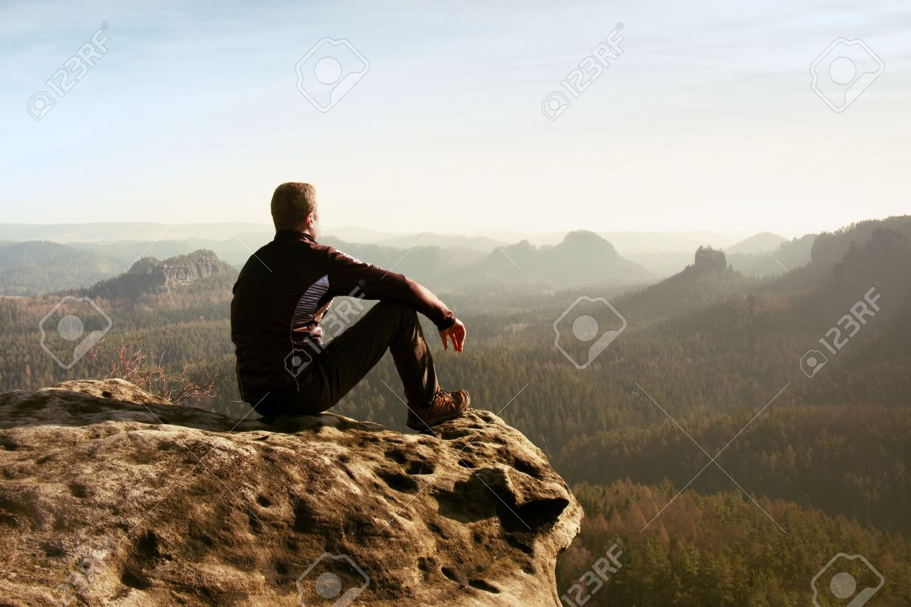 Young man in black sportswear is sitting on cliff's edge and looking to misty valley bellow - 47642824