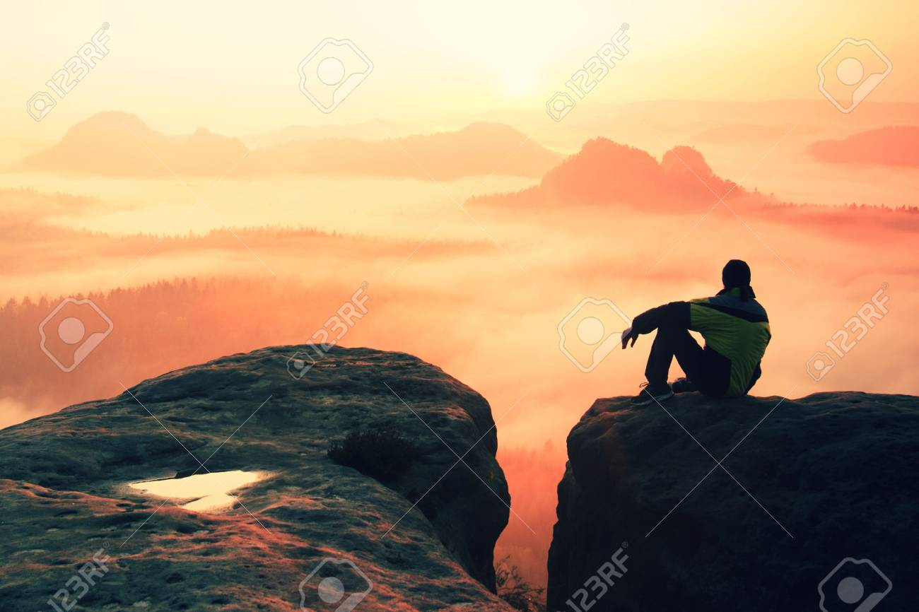 Rear view of male hiker sitting on the rocky peak while enjoying a daybreak above mounrains valley - 47737249