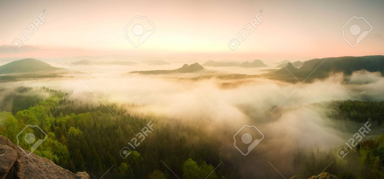 Landscape misty panorama. Fantastic dreamy sunrise on rocky mountains with view into misty valley below - 47737427
