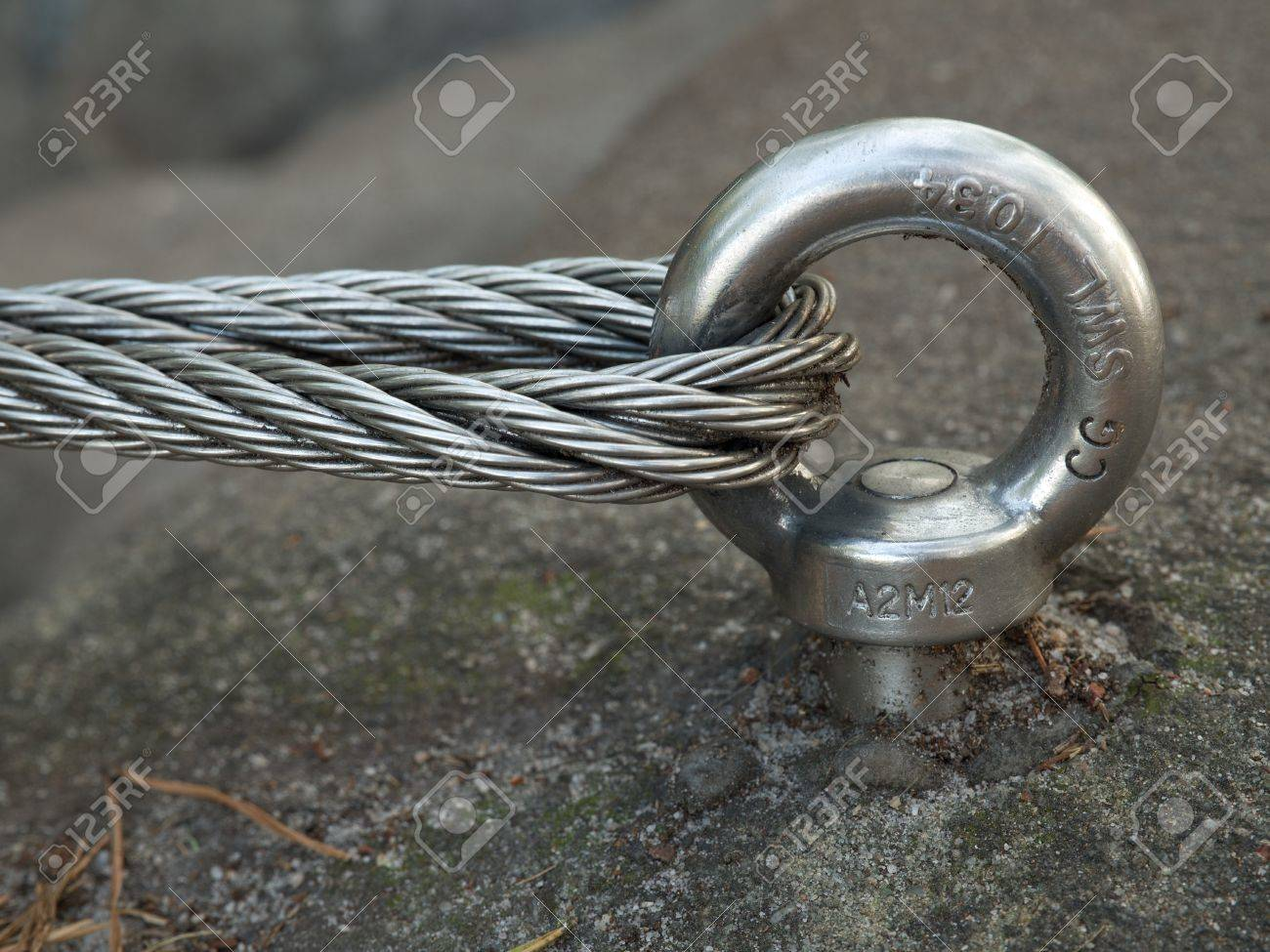 Detail of steel bolt anchor eye in sandstone rock. The end knot of steel rope. Climbers path via ferrata. Iron twisted rope fixed in block. - 47937736