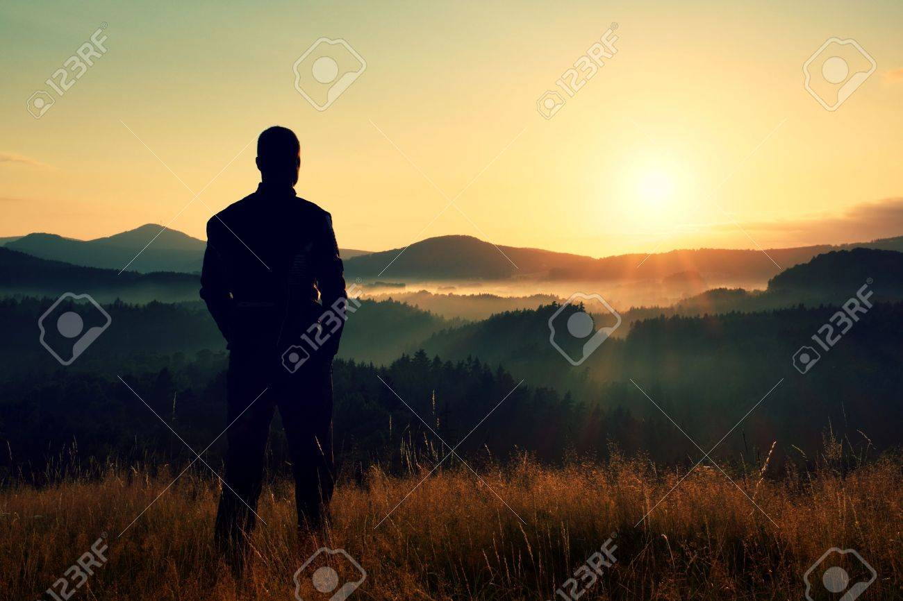 Tall hiker stand on meadow with golden stalks of grass and watch over misty and foggy morning valley to sunrise - 47937216