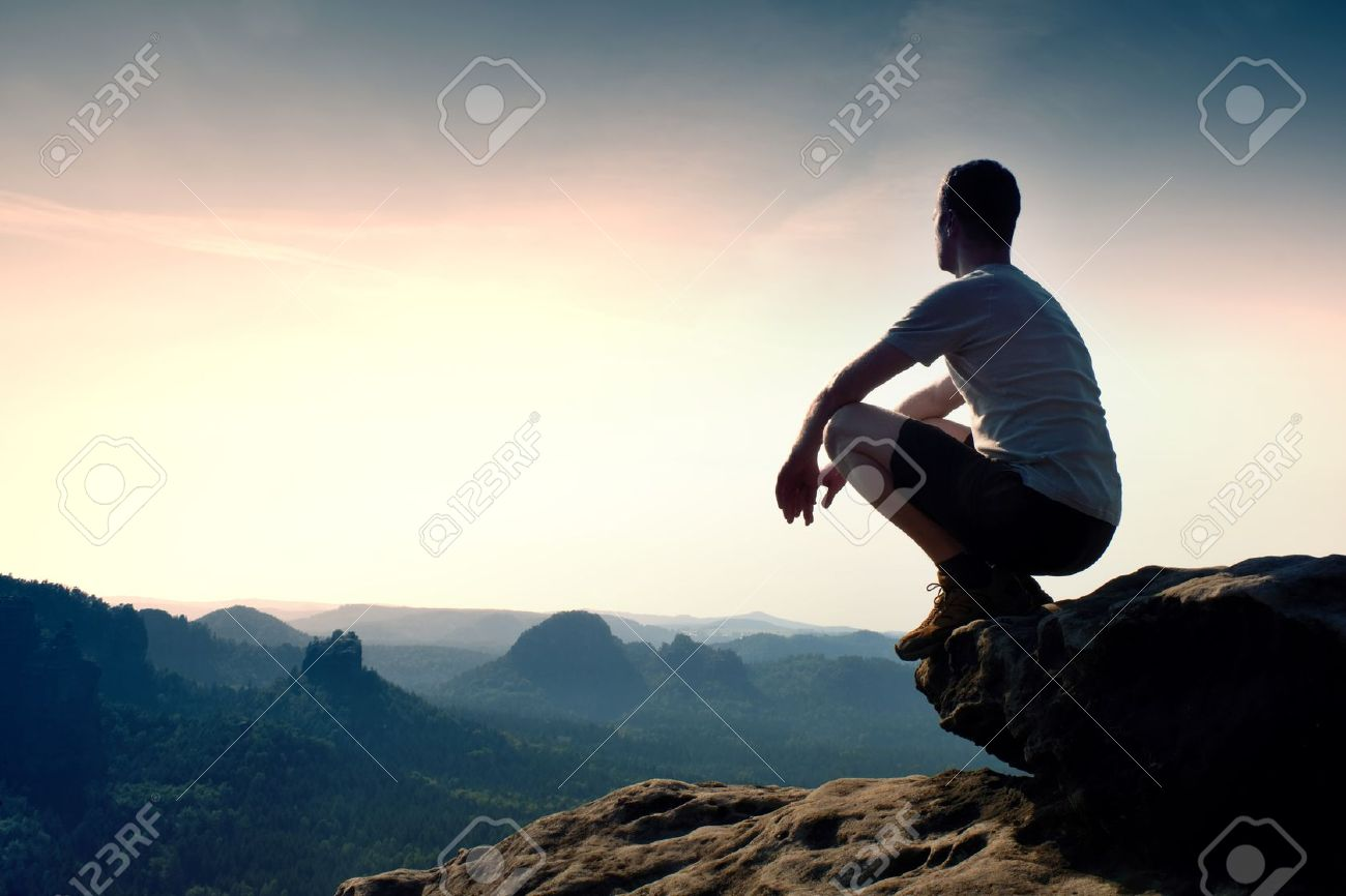 Young hiker in black pants and shirt is sitting on cliff's edge and looking to misty hilly valley bellow - 47931962