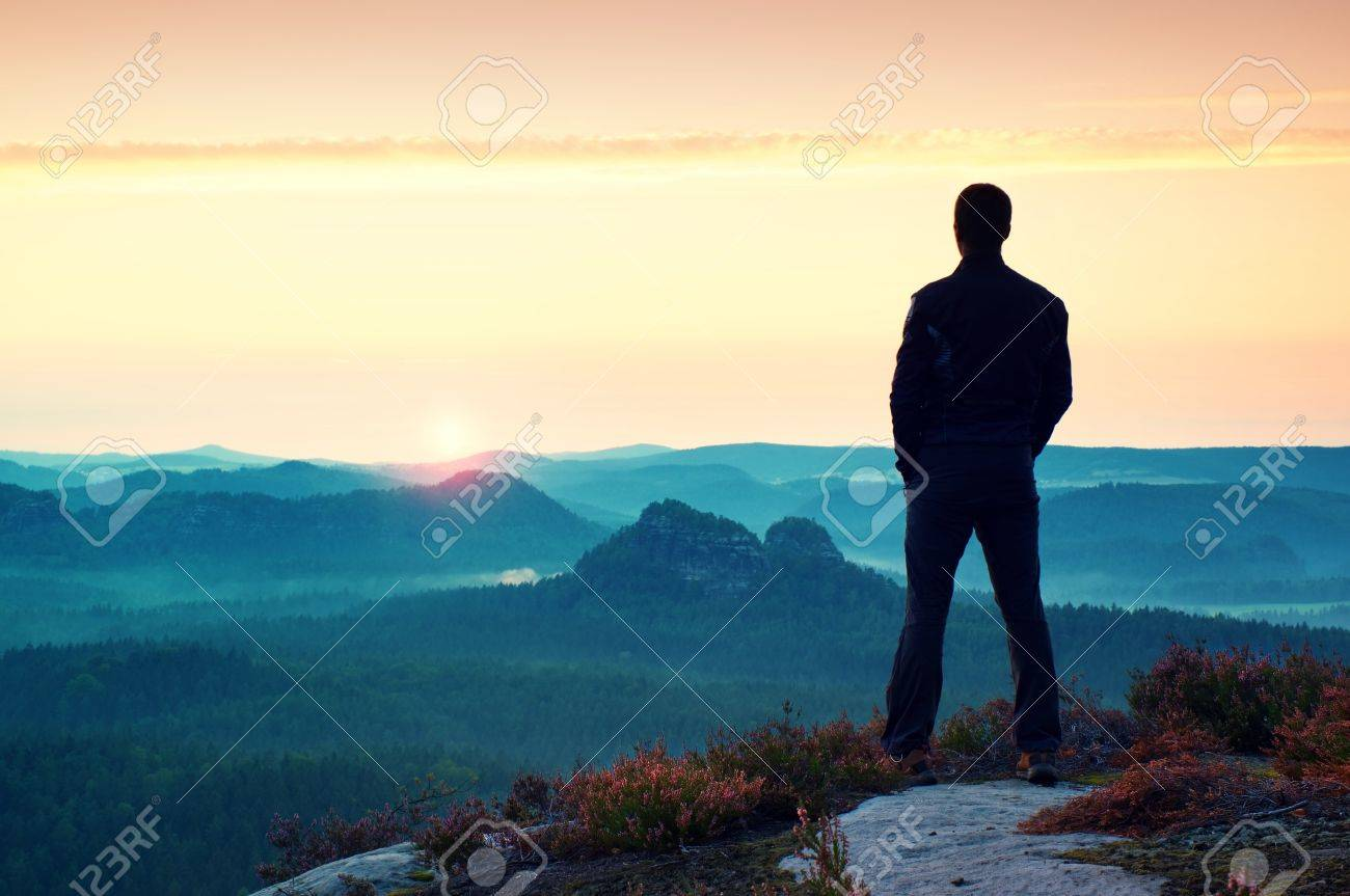 Hiker in sportswear stand on the peak of sandstone rock in rock empires park and watching over the misty and foggy morning valley to Sun. Beautiful moment the miracle of nature - 47931664