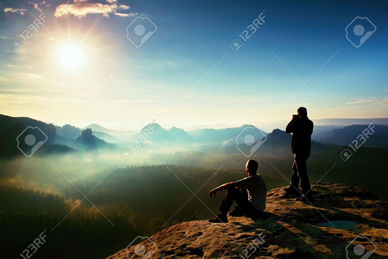Hiker and photo enthusiast stay with tripod on cliff and thinking. Dreamy fogy landscape, blue misty sunrise in a beautiful valley below - 48090991