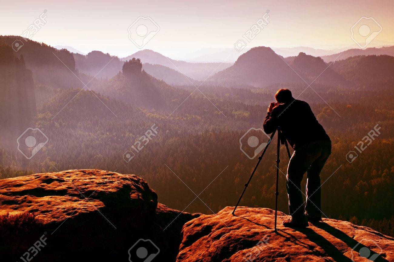 Professional on cliff. Nature photographer takes photos with mirror camera on peak of rock. Dreamy fogy landscape, spring orange pink misty sunrise in a beautiful valley below. - 48092113