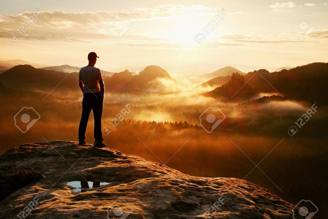 Hiker in red cap stand on the peak of sandstone rock in rock empires park and watching over the misty and foggy morning valley to Sun. Beautiful moment the miracle of nature - 48101909