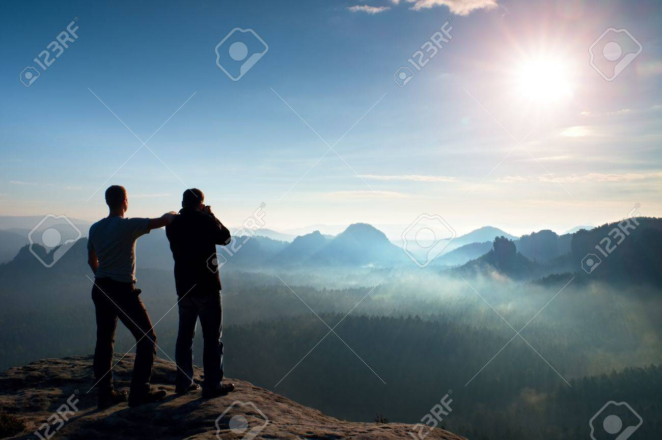 Hiker and photo enthusiast stay on cliff and thinking. Dreamy fogy landscape, blue misty sunrise in a beautiful valley below - 48121489