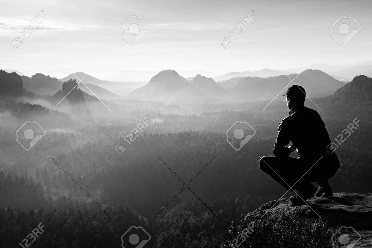 Runner in red cap and in dark sportswear in squatting position on a rock, enjoy the scenery - 48121679