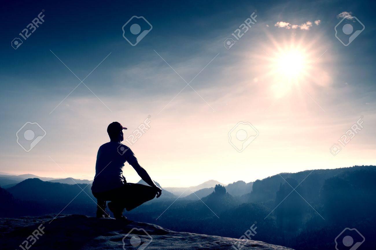 Runner in red cap and in dark sportswear in squatting position on a rock in heather bushes, enjoy the scenery - 48121675