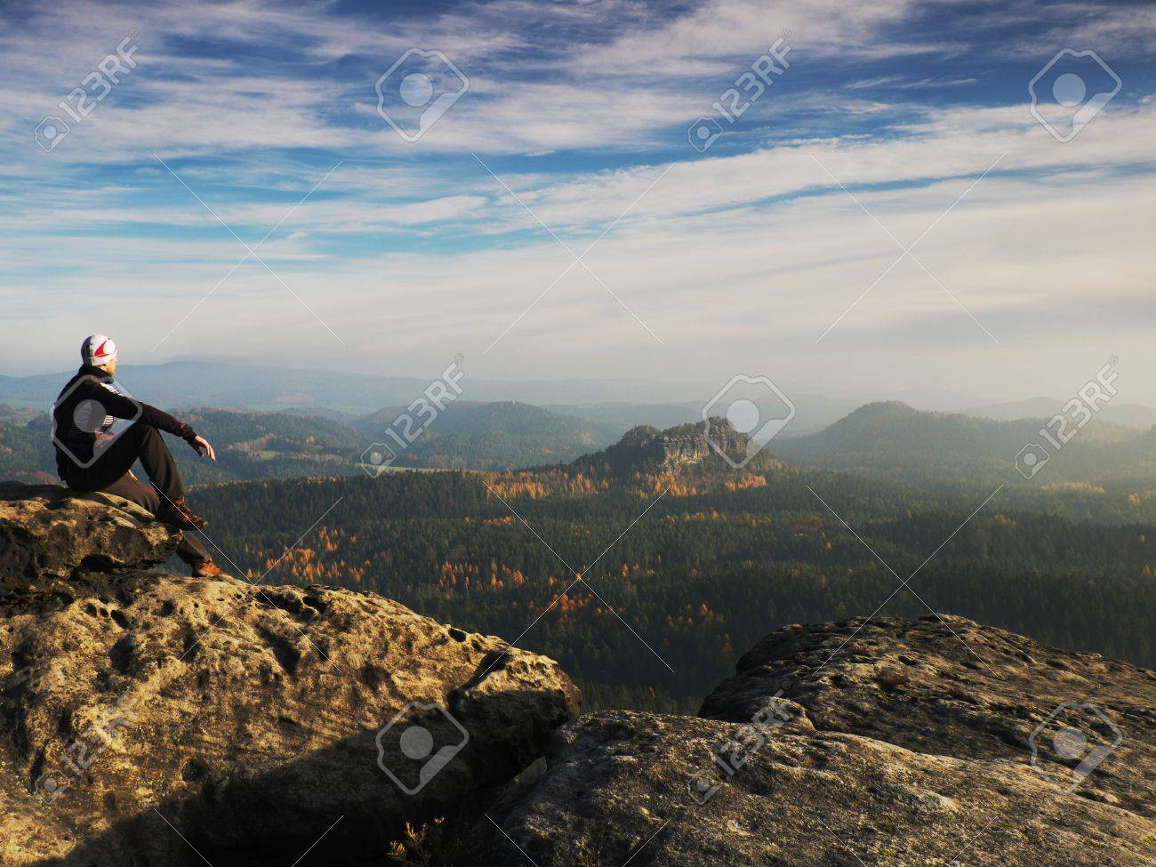 Young man in black sportswear is sitting on cliff's edge and looking to misty valley bellow - 49062817