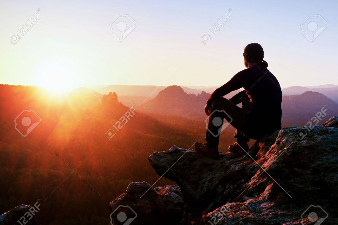Adult tourist in black trousers, jacket and dark cap sit on cliff's edge and looking to misty hilly valley bellow - 50043269