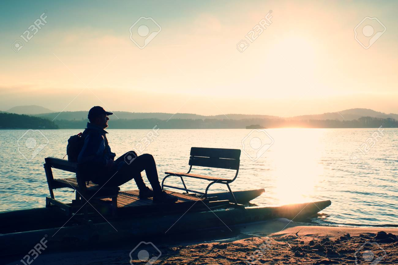 Man sit on abandoned rusty pedal boat stuck on sand of beach