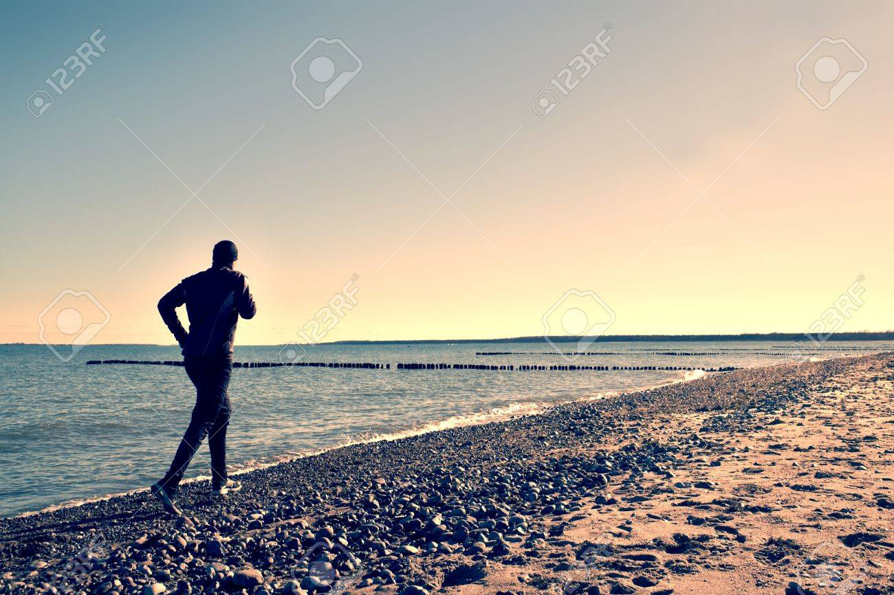 Silhouette of tall man in black running and exercising on stony beach at breakwater. Vivid and strong vignetting effect - 55382972