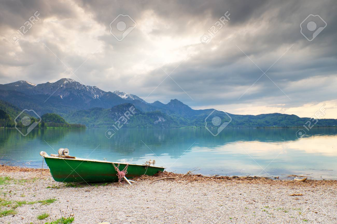 Abandoned fishing paddle boat on bank of Alps lake. Morning lake glowing by sunlight. Dramatic and picturesque scene. Mountains in water mirror. - 57570244