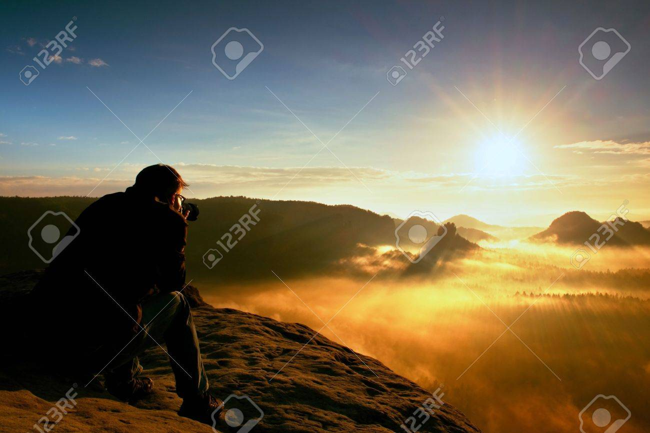 Happy photo enthusiast is enjoying fantastic miracle of nature on cliff on rock. Dreamy fogy landscape, blue misty sunrise in a beautiful valley below - 57570603