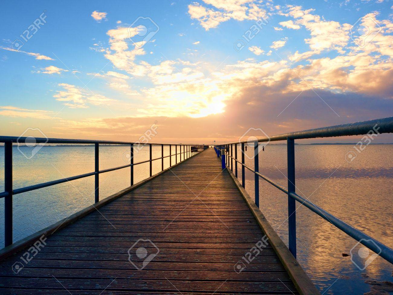 Morning in harbor. Touristic mole, wet pier construction above sea. Sunny clear blue sky, smooth water level - 68079597